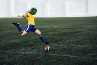 Young woman playing football on football ground shooting the ball - VPIF00517