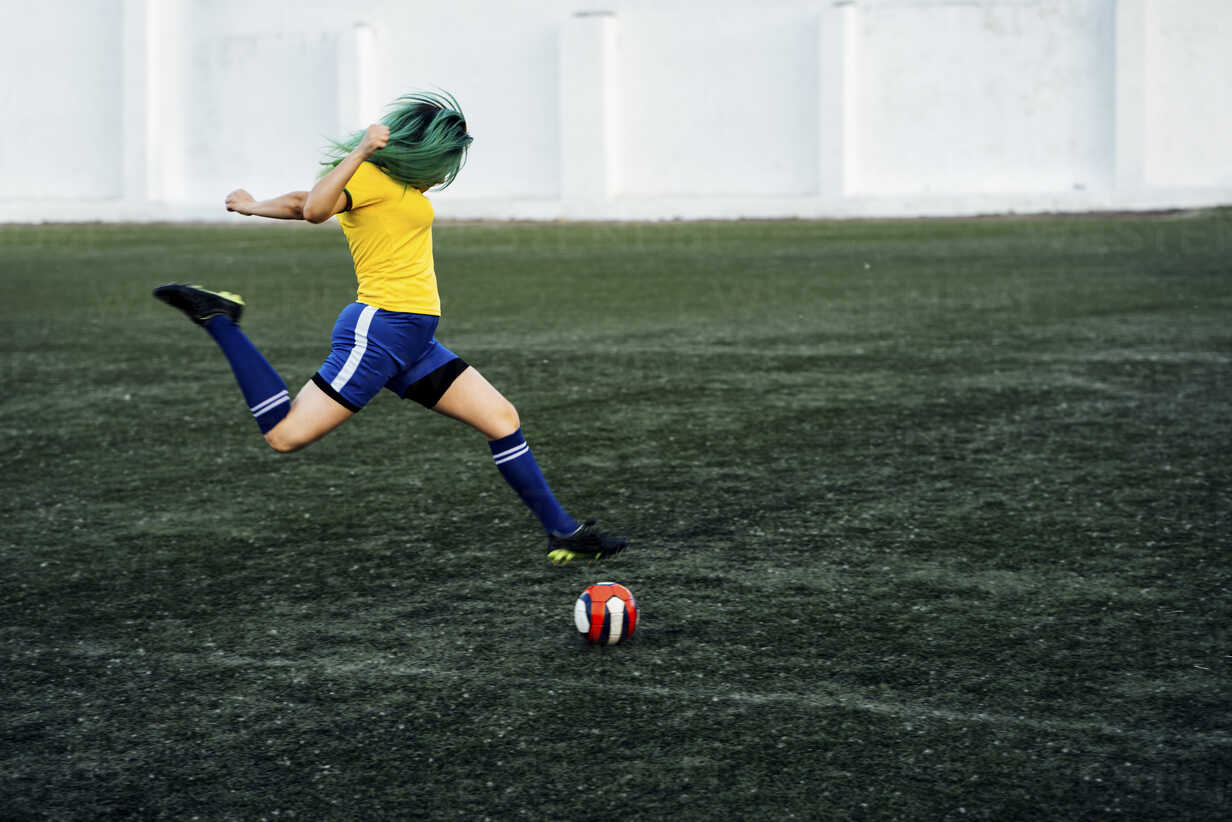 Young woman playing football on football ground shooting the ball - VPIF00517 - Vasily Pindyurin/Westend61
