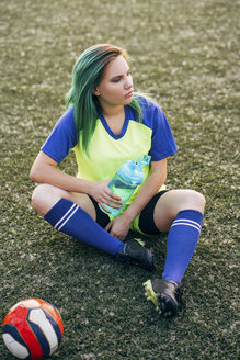 Young woman sitting on football ground with water bottle and ball - VPIF00520