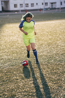 Young woman playing football on football ground running with the ball - VPIF00523