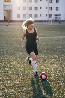 Young woman playing football on football ground running with the ball - VPIF00526
