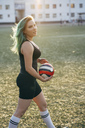 Young woman walking on football ground holding the ball - VPIF00529