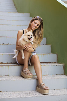Smiling young woman sitting on stairs, holding her dog - ACPF00246