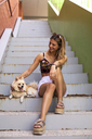 Pretty young woman smiling, caressing a dog - ACPF00255