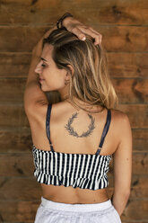 Pretty blond young woman, wooden wall, tattooed, wreath - ACPF00264