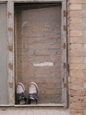Pair of shoes in a bricked window - JMF00417