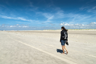 Germany, Schleswig-Holstein, Sankt Peter-Ording, woman walking on the beach at low tide - UMF00846