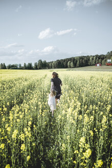 Back view of little girl walking with her mother in rape field - PSIF00012