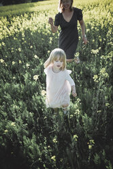 Portrait of little girl walking on rape field with her mother - PSIF00018