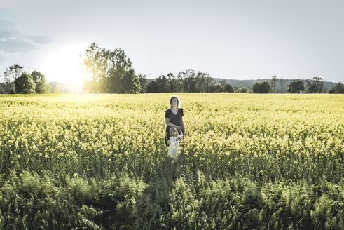 Mother and lttle daughter walking in rape field - PSIF00021