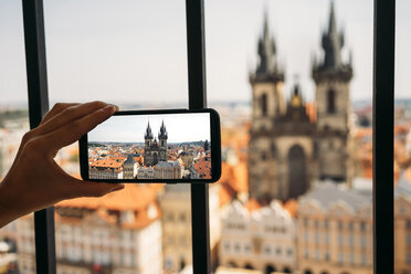 Czechia, Prague, woman taking photo of Church of Our Lady from old town hall with smartphone, partial view - GEMF02304