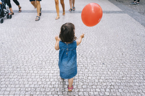 Back view of baby girl with red balloon walking on pavement - GEMF02307