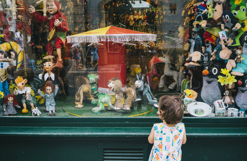 Czechia, Prague, back view of little girl standing in front of toy shop looking at puppets - GEM02325
