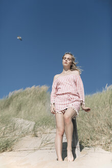 Young woman leaning on a fence post on beach dune - JESF00115