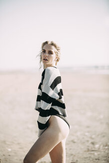 Portrait of a young woman standing on the beach wearing a pullover - JESF00124