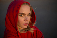 Portrait of young woman wearing red hooded jacket in evening light - JESF00136