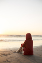 Young woman wearing red hooded jacket sitting on the beach at sunset - JESF00139