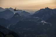 Austria, Salzburg State, Loferer Steinberge, helicopter in mountainscape at twilight - HAMF00360