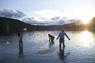 Three young adults smile while splashing water at sunset in Idaho. - AURF01412