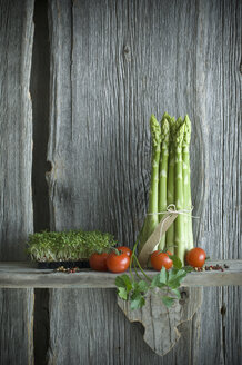 Bundle of green asparagus, tomato, cress, parsley and mixed pepper on wood - ASF06204
