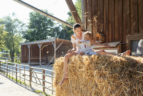 Happy mother and little daughter playing with straw in a barn - DIGF04964