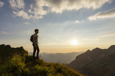 Germany, Bavaria, Oberstdorf, man on a hike in the mountains looking at view at sunset - DIGF04985