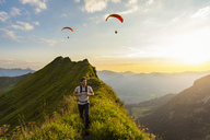 Germany, Bavaria, Oberstdorf, man on a hike in the mountains at sunset with paraglider in background - DIGF04988