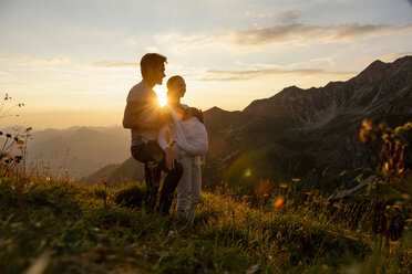 Germany, Bavaria, Oberstdorf, family with little daughter on a hike in the mountains at sunset - DIGF04991