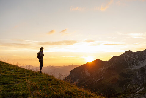 Germany, Bavaria, Oberstdorf, man on a hike in the mountains looking at view at sunset - DIGF04994