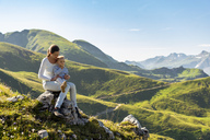 Germany, Bavaria, Oberstdorf, mother and little daughter on a hike in the mountains having a break - DIGF05000