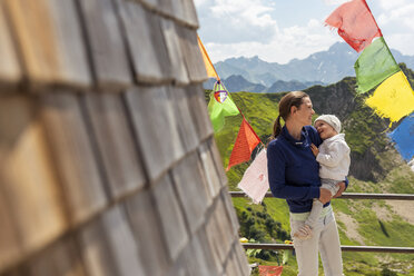Germany, Bavaria, Oberstdorf, happy mother carrying little daughter on a mountain hut surrounded by pennants - DIGF05003