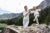 Germany, Bavaria, Oberstdorf, mother helping little daughter balancing on a log - DIGF05006
