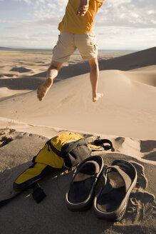 Man jumps in sand dunes. - AURF01432