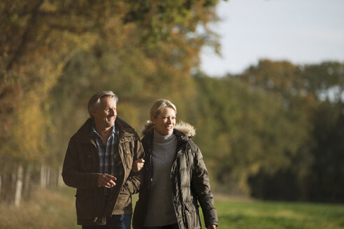Mature couple walking arm in arm in sunny autumn park - HOXF03675