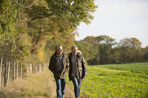 Mature couple walking arm in arm in sunny, rural autumn field - HOXF03717