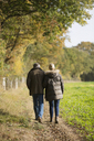 Affectionate mature couple walking in sunny, rural autumn field - HOXF03732