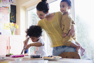Mother helping toddler daughter cutting breakfast waffles - HOXF03765
