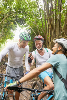 Male friends mountain biking, using smart phone in woods - CAIF21320