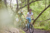 Men mountain biking on trail in woods - CAIF21326