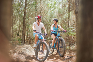 Father and daughter mountain biking on trail in woods - CAIF21332