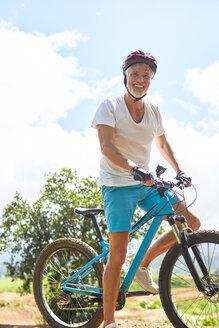 Portrait smiling, confident mature man mountain biking - CAIF21338