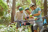 Friends mountain biking, using wearable camera in woods - CAIF21344