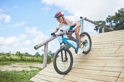 Focused mature man mountain biking down obstacle course ramp - CAIF21350