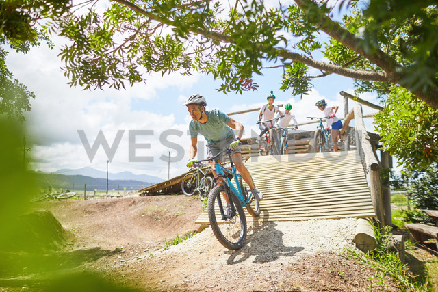 Man mountain biking down sunny obstacle course ramp - CAIF21353