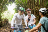 Male friends mountain biking, using smart phone in woods - CAIF21356