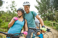 Happy, affectionate young couple mountain biking - CAIF21359