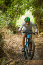 Happy man mountain biking on trail in woods - CAIF21371