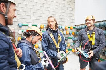 Smiling friends preparing zip line equipment - CAIF21404