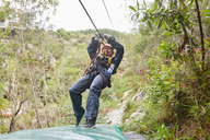 Woman zip lining among trees - CAIF21407