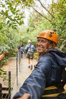 Portrait happy, muddy woman enjoying zip lining - CAIF21425